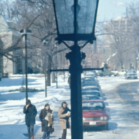 Winter on campus, streetscape with lamp in foreground