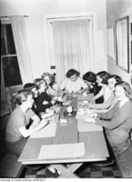Members of the Alpha Phi Fraternity around the table.
