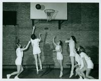 Jan (Thayer) Tennant (2nd from left) attempts a baske as part of a III PHE women's basketball team, 1957-1958